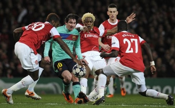 Arsenal's Johan Djourou, at left, with teammates Alex Song, centre and Emmanuel Eboue, at right, challenge for the ball with Barcelona's Lionel Messi during a Champions League, round of 16, first leg soccer match at Arsenal's Emirates stadium in London, Wednesday, Feb. 16, 2011. (AP Photo/Tom Hevezi)